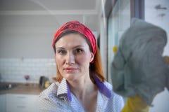 Vrouw die huishoudelijk werk doet Huisvrouw Portrait While Cleaning Foto door het glas royalty-vrije stock afbeelding