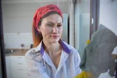 Vrouw die huishoudelijk werk doet Huisvrouw Portrait While Cleaning Foto door het glas royalty-vrije stock foto's