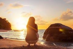 Vrouw die hurkende oefening op zandig strand doen stock afbeelding