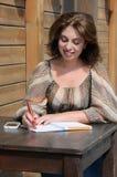 Vrouw die iets schrijven aan het notitieboekje die pen gebruiken Royalty-vrije Stock Foto's