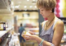 Vrouw die informatie over pakket in supermarkt controleren Stock Afbeeldingen