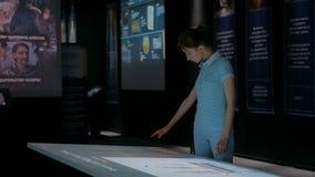 Vrouw die interactieve touchscreen vertoning gebruiken bij modern geschiedenismuseum stock video