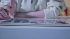 Vrouw die interactieve touchscreen vertoning gebruiken bij stedelijke tentoonstelling die - en scrollen wat betreft vermaak en te stock footage