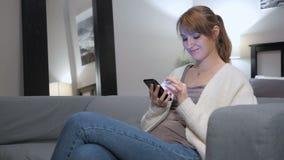 Vrouw die Internet op Smartphone doorbladeren, die op Laag zitten stock footage