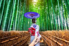 Vrouw die Japanse traditionele de man ` s van de kimonoholding hand dragen en hem leiden tot Bamboebos in Kyoto, Japan stock foto's