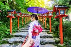 Vrouw die Japanse traditionele de man ` s van de kimonoholding hand dragen en hem leiden tot Kifune-heiligdom, Kyoto in Japan stock afbeeldingen