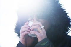 Vrouw die in jasje met een kap hete koffie in openlucht drinken Royalty-vrije Stock Afbeeldingen