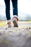 Vrouw die in jeans en laarzen langs een landelijke weg loopt Stock Foto