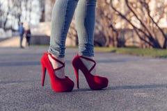 Vrouw die jeans en rode hoge hielschoenen dragen De vrouwen dragen hoge hielen die zich op de weg bevinden Sexy benen in rode hog Royalty-vrije Stock Foto's