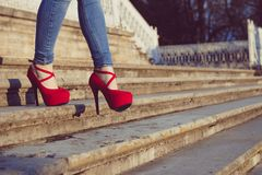 Vrouw die jeans en rode hoge hielschoenen in oude stad draagt De vrouwen dragen hoge hielengang op treden Sexy benen in rode hoge Stock Afbeelding