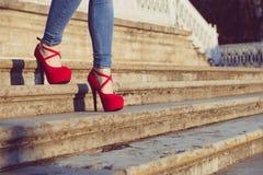 Vrouw die jeans en rode hoge hielschoenen in oude stad draagt De vrouwen dragen hoge hielengang op treden Sexy benen in rode hoge Stock Foto's