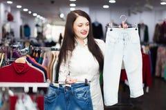 Vrouw die jeans kiezen bij opslag Royalty-vrije Stock Fotografie
