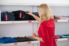 Vrouw die Jeans in Opslag kiezen Royalty-vrije Stock Foto