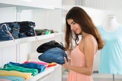 Vrouw die Jeans in Opslag kiezen Stock Afbeelding
