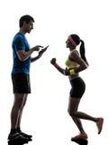 Vrouw die joggingman bus uitoefenen die digitale tablet gebruiken silhoue stock foto's