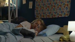 Vrouw die jongen krijgen aan bed in nacht stock video