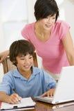 Vrouw die jongen met laptop helpt die thuiswerk doet Stock Foto