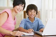 Vrouw die jongen met laptop helpt die thuiswerk doet Stock Afbeeldingen