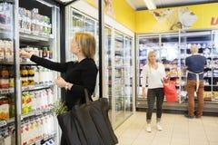 Vrouw die Juice Packets While Carrying Shopping-Zak kiezen Stock Foto's