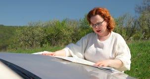 Vrouw die juiste richting zoeken die document kaart op bonnet gebruiken stock video