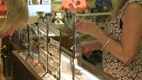 Vrouw die juwelen bij een boutique bekijken stock video
