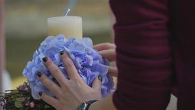 Vrouw die kaarsen met bloemen voor huwelijk verfraaien stock video