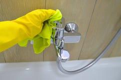 Vrouw die karweien in badkamers doen, het schoonmaken van waterkraan beeld royalty-vrije stock afbeelding