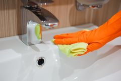 Vrouw die karweien in badkamers doen, die kraan schoonmaken stock fotografie