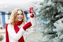Vrouw die Kerstboom buiten verfraaien Stock Afbeeldingen