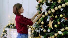 Vrouw die Kerstboom verfraaien door gouden stuk speelgoed in de ruimte stock videobeelden