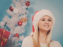 Vrouw die in Kerstmanhoed over Kerstmis denken Royalty-vrije Stock Foto's