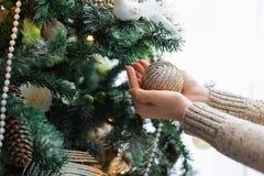 Vrouw die Kerstmisboom, de nieuwe achtergrond van de jaardecoratie verfraaien Stock Fotografie