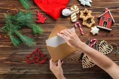Vrouw die Kerstmisbrief zetten in envelop Royalty-vrije Stock Foto's