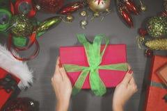 Vrouw die Kerstmisgiften op de lijst zetten stock afbeeldingen