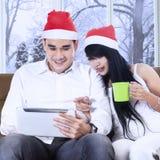 Vrouw die in Kerstmishoed op tablet richten Stock Foto's