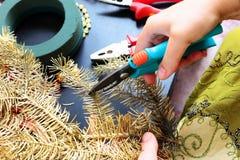 Vrouw die Kerstmiskroon maakt Stock Afbeeldingen