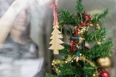 Vrouw die Kerstmisornament opzetten die thuis een houten tre houden stock afbeeldingen