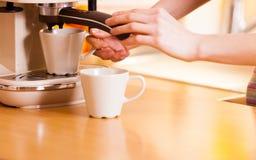 Vrouw die in keuken koffie van machine maken Stock Afbeelding