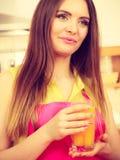 Vrouw die in keuken vers jus d'orange drinken royalty-vrije stock foto