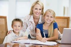Vrouw die kinderen met laptop helpt die thuiswerk doet royalty-vrije stock fotografie