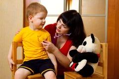 Vrouw die kindjongen onderzoekt Stock Fotografie