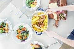 Vrouw die kip met aardappelschotel voorbereiden, platen van plantaardige salade Royalty-vrije Stock Fotografie