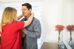 Vrouw die klaar haar echtgenoot helpen voor het werk te worden stock afbeelding