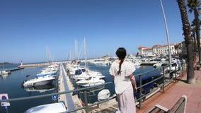Vrouw die in kleding in een Mediterrane haven met velen plezierboot, Frankrijk lopen stock videobeelden