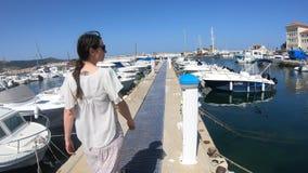 Vrouw die in kleding in een Mediterrane haven met velen plezierboot, Frankrijk lopen stock video