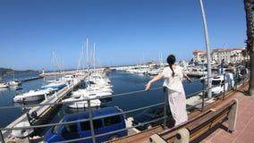 Vrouw die in kleding in een Mediterrane haven met velen plezierboot, Frankrijk lopen stock footage