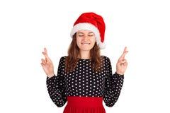 Vrouw die in kleding, sluitende ogen en het opheffen van gekruiste vingers terwijl het bidden en het hopen ruim glimlachen emotio stock foto