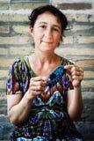 Vrouw die kleine gebreide schoenen voor jonge geitjes maken royalty-vrije stock afbeeldingen