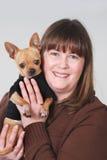 Vrouw die kleine hond, Chihuahua houdt Royalty-vrije Stock Foto