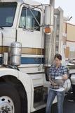 Vrouw die klembord bekijken terwijl status door flatbed vrachtwagen royalty-vrije stock foto's